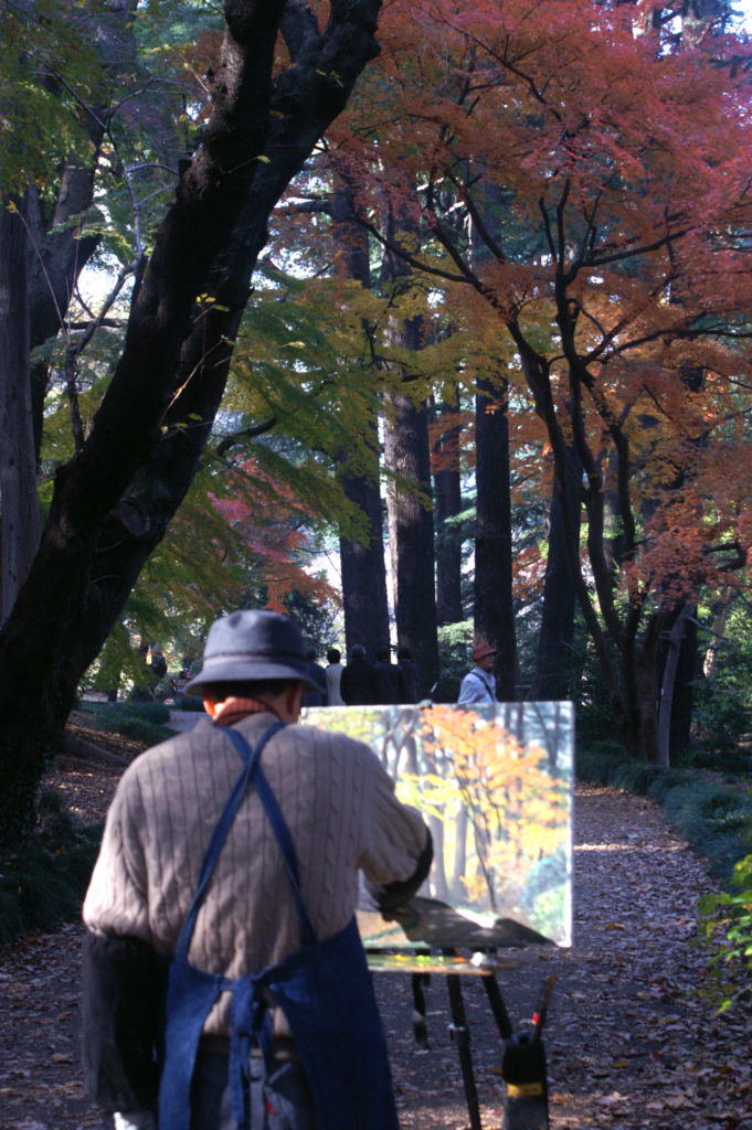 A Japanese painter painting an image of the autumn foliage.